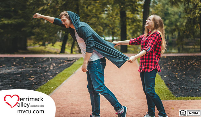 smiling teenage girl holding back of sweatshirt of teenage boy like a cape as he leans forward in a superhero pose with his fist in the air like he's flying