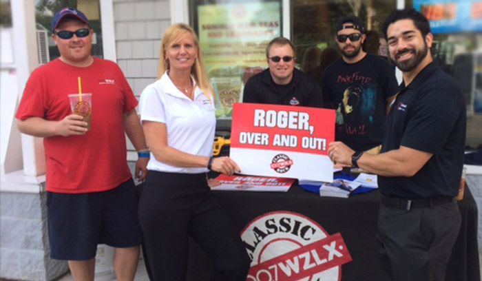 "5 people standing by the display table for 100.7 WZLX, holding a sign that says ""ROGER, OVER AND OUT!"""